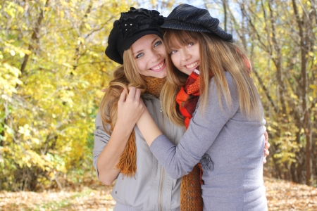 two smiling teenage girls hugging in the autumn park photo