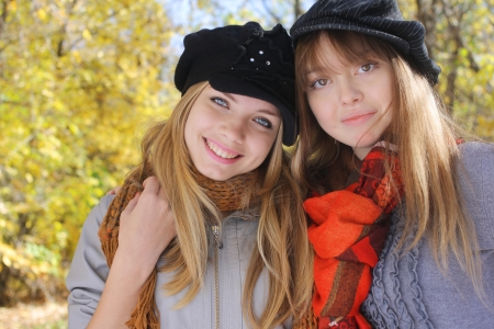 outdoor portrait of two young women in autumnal park photo