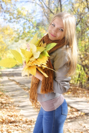Young beautiful girl holding a bunch of leaves in autumn park photo
