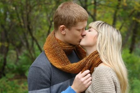 young couple kiss: joven pareja se besa en la temporada de oto�o Foto de archivo
