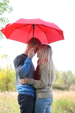 young couple man and woman smiling under red umbrella autumn photo