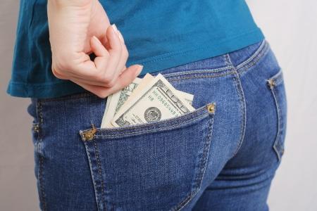 Hundred dollar bills in the back pocket of jeans girl Imagens