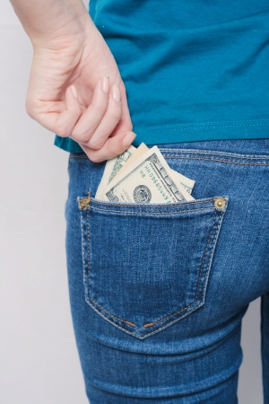 hand holding dollar currency cash taking  out bank note of jeans pocket photo