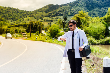 Asia young docter are looking watch at rural road .Community Health and Development Hospital In Remote Areas Development Fund Concept. Archivio Fotografico