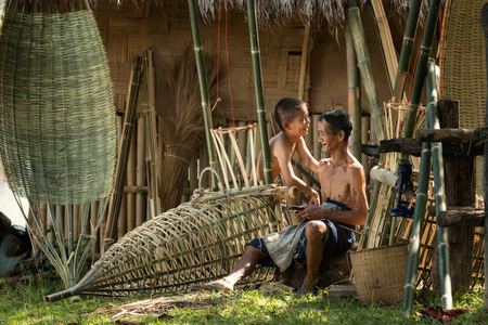 basketry: Father and son with a rustic career living in the countryside.Farmer thailand,Handmade craftsmanship of rattan chair craftsmen in rural Thailand. Stock Photo