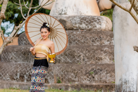 Asia girl wearing a national Thai costume,Asian girl Beautiful girl in Laos costume.,Laos traditional suit,woman wearing typical Thai dress at temple.