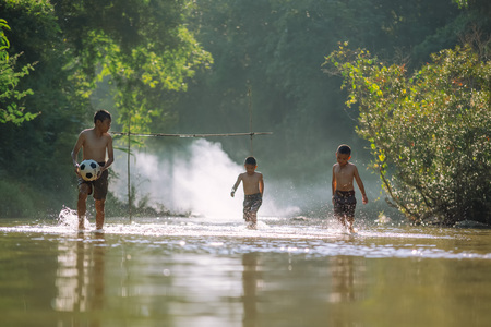 Asian children play soccer in the river,Sport plays an important role in rural and regional Thailand,Sport are the predominantly or exclusively played in rural areas,Thailand football.