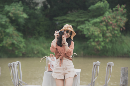 Young women are holding the camera sitting on the wooden bridge and river on background.And looking at beautiful view