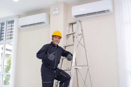 The mechanic Technician are Repairing Air Conditioner in room. Archivio Fotografico
