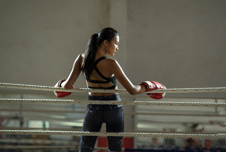 Upset young fighter boxer girl wearing boxing gloves in gymมFemale boxer taking a break from her practice.