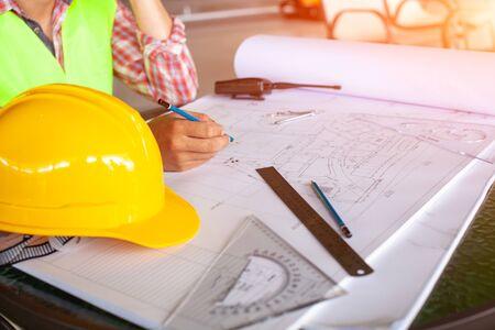 Konzeptarchitekten, Ingenieur, der Stift zeigt, der Ausrüstungsarchitekten hält Auf dem Schreibtisch mit einer Blaupause im Büro, Vintage, Sonnenunterganglicht. Selektiver Fokus. Standard-Bild