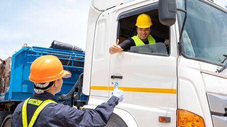 Caposquadra con cappelli di sicurezza e giubbotto di sicurezza sta portando un documento di ispezione dell'auto nel parcheggio con i camionisti, concetto di pianificazione della giornata lavorativa. Archivio Fotografico