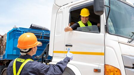 Foreman with safety hats and safety vest is carrying a car inspection document in the parking with truck drivers,Concept of planning work day. Stock Photo