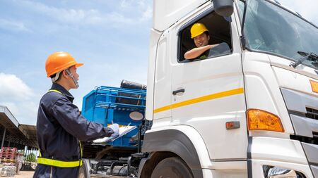 Foreman with safety hats and safety vest is carrying a car inspection document in the parking with truck drivers,Concept of planning work day.