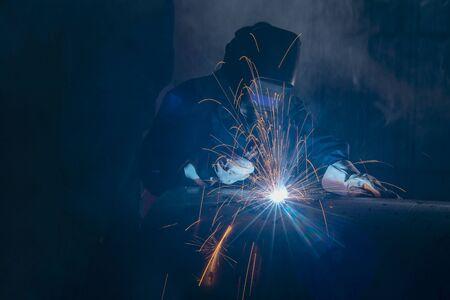 Soldador profesional y tubo de metal de soldadura de máscara en la mesa industrial.