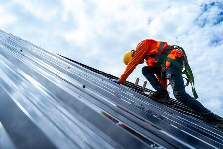 Dekarz pracujący na konstrukcji dachu budynku na placu budowy, dekarz za pomocą pneumatycznego lub pneumatycznego pistoletu do gwoździ i instalowanie blachy na nowym dachu.
