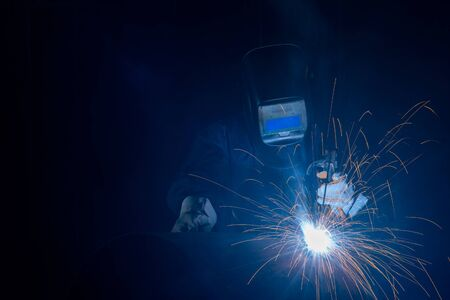 Professional welder and mask welding metal pipe on the industrial table.A welder is a tradesperson who specializes in fusing materials together. Stock Photo
