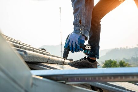 Engineers worker install new CPAC roof,Roofing tools,Electric drill used on new roofs with CPAC roof,Construction concepts. Standard-Bild