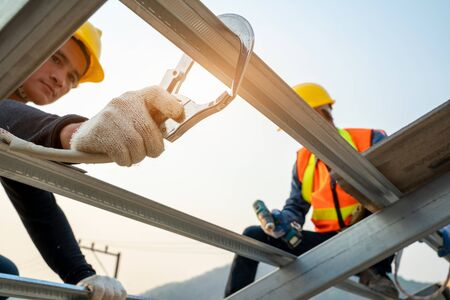 Construction worker wearing safety harness belt during working at high place and installing concrete roof tile on top of the new roof,Concept of residential building under construction.