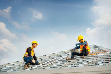 Construction worker wearing safety harness belt during working on roof structure of building on construction site,Roofer using air or pneumatic nail gun and installing concrete roof tile on top new roof.