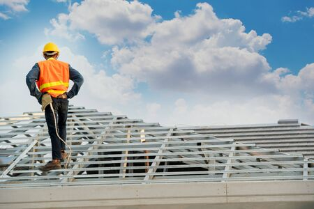 Construction worker wearing safety harness belt during working installing concrete roof tile on top of the new roof,Concept of residential building under construction.