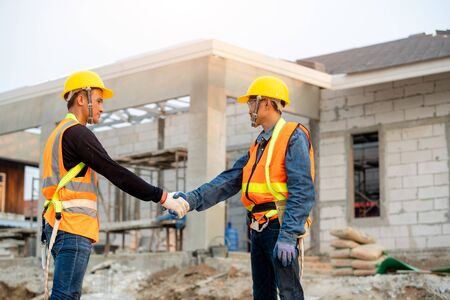 Engineers shaking hands at construction site,Concept of residential building under construction.