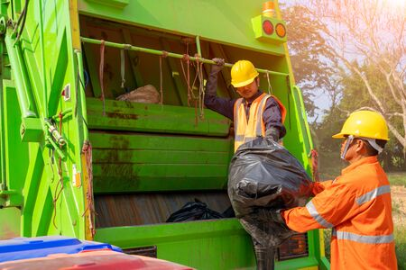Two garbage men working together on emptying dustbins for trash removal with truck loading waste and trash bin. Archivio Fotografico