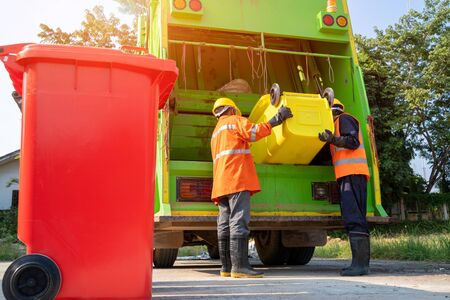 Two garbage men working together on emptying dustbins for trash removal with truck loading waste and trash bin. Imagens