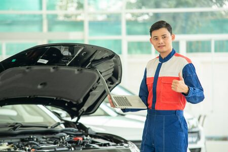 Mechanic perform vehicle checkup and use notebook computers to record engine checks,Concept of working in a car service center.