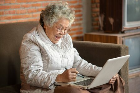 Happy Asian retired woman use notebook in living room at home.