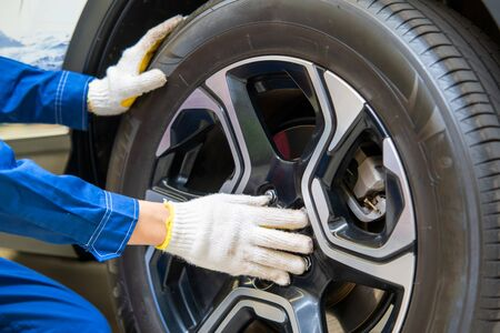 Car mechanic changing tire in professional car repair,Car Maintenance in the Professional Service.
