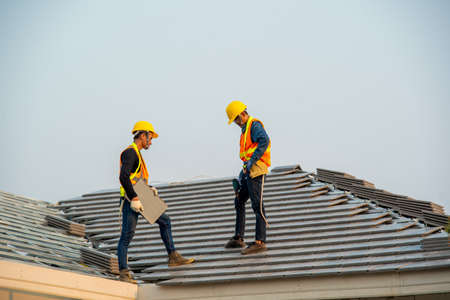 Roofer working on roof,Professional roofer are installing new roof on top roof of modern house. Zdjęcie Seryjne