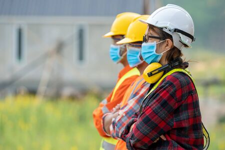 Group of Asian engineers wearing protective mask to Protect Against Covid-19 with helmet safety in the construction site,Coronavirus has turned into a global emergency,Safety concept.