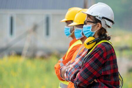 Grupo de ingenieros asiáticos que usan máscara protectora para protegerse contra Covid-19 con casco de seguridad en el sitio de construcción, el coronavirus se ha convertido en una emergencia global, concepto de seguridad.
