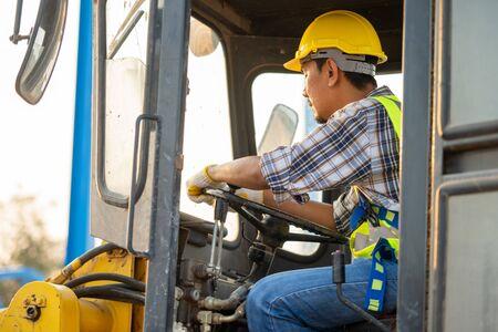 Baufahrer, der Baggerlader auf der Baustelle fährt, Geschäfts- und Baukonzept.