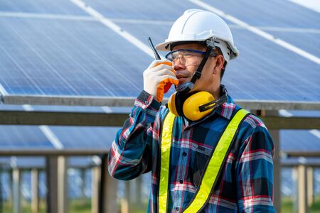 Engineer checking solar panel in routine operation at solar power plant,Solar power plant to innovation of green energy for life adjustment. Stock Photo