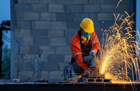 Worker with metal grinding on steel,Metal grinding on steel pipe with flash of sparks. Stockfoto