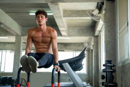 Sportsman exercising on parallel bars in the gym,Athlete builder muscles lifestyle.