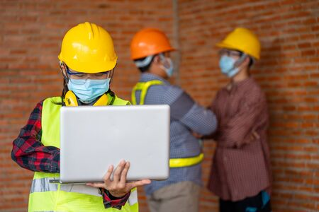 Engineer women wear protective face masks for safety Coronavirus Disease 2019 (COVID-19) use laptop for work at construction site,Coronavirus has turned into a global emergency. Foto de archivo