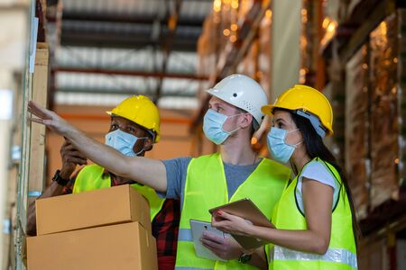Group warehouse workers wearing protective mask to Protect Against Covid-19 working together at warehouse,Coronavirus has turned into a global emergency. Stock Photo
