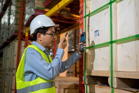 Worker working use radio to communicate in the large warehouse,Wholesale,Logistic,People and export concept.