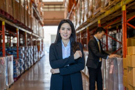 Portrait of business women with crossed arms standing in a large warehouse.