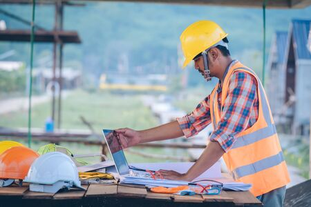 Engineer working with laptop and blueprints,engineer inspection in construction site for architectural plan,sketching a construction project.