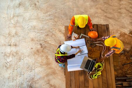Team of engineer and architects working, meeting, discussing,designing, planning, measuring layout of building blueprints at construction site,Top view,Construction concept. Banco de Imagens