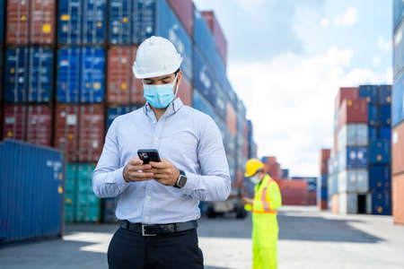 Business man wearing protective mask to Protect Against Covid-19 worker checking container box with use smart phone in shipping yard, Control loading unloading container box freight. Reklamní fotografie