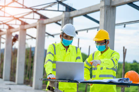 Two engineers wearing protective mask to Protect Against Covid-19 and checking production process in building construction site,Construction,Building, teamwork and people concept.