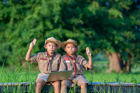 Young American Boy Scouts use laptop at scout camp during their summer camp.