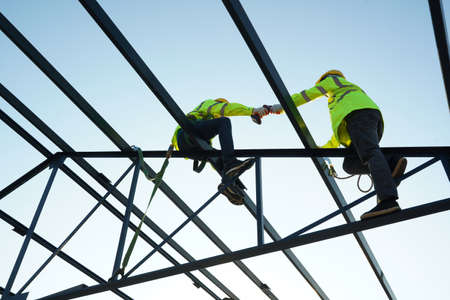 Construction workers wearing safety harness belt working at high place at building site. Stock fotó