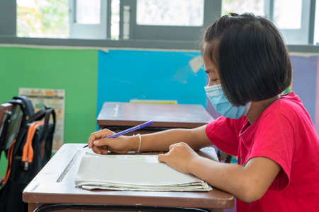 Asian elementary school wear mask for protect corona virus desk trying to find new ideas for schoolwork,Education,Elementary school, Learning and people concept. Foto de archivo