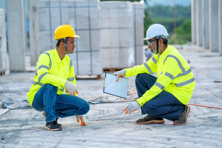 Construction engineer team with clipboard checking work with at construction site. Banco de Imagens